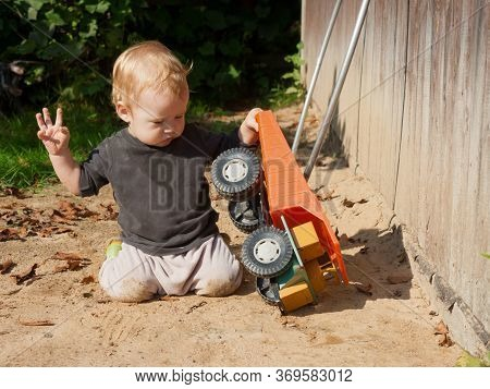 Little Boy Kneels On The Sand In The Courtyard Of The House And Plays With A Huge Toy Dump Truck.