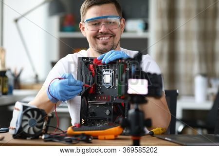 Man Removes Computer Repair On Camcorder For Blog. Installation Purchased Device. Guy Is Teaching On