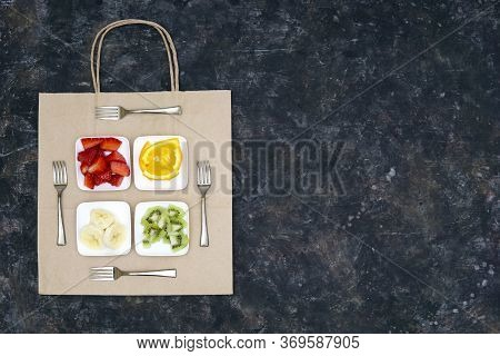 Creative Arrangement Of Four Small Plates With Sliced Fruits And Four Forks On A Flat Paper Shopping