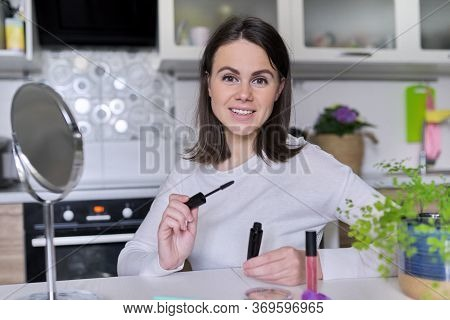 Young Attractive Woman Doing Makeup, Female Sitting At Home At Table In Kitchen With Cosmetic Produc