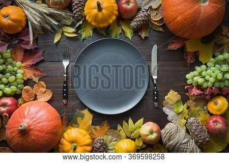 Fall Table Place Setting With Dry Leaves And Pumpkins. Centerpieces Thanksgiving Day. View From Abov