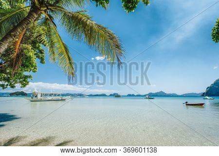 El Nido, Palawan Island, Philippines. Palm Trees Of Corong Corong Beach, Island Hopping Boats In Blu
