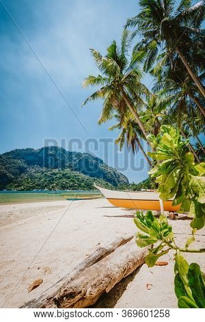 Philippines Beach Landscape - Local Banca Boat Under Palm Trees At Corong Corong Beach In El Nido, P