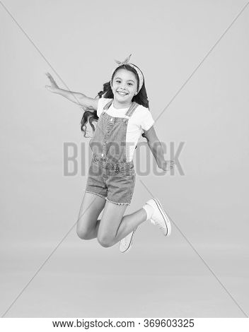 Jump Of Happiness. Small Girl Jump Yellow Background. Full Of Energy. Active Girl Feel Freedom. Fun