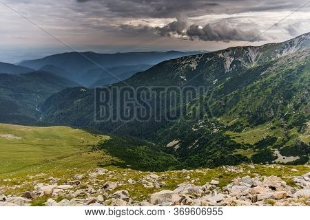 Rainy Clouds Over The Green Summer Forest In The Parang Romanian Mountains As Seen From The Transalp