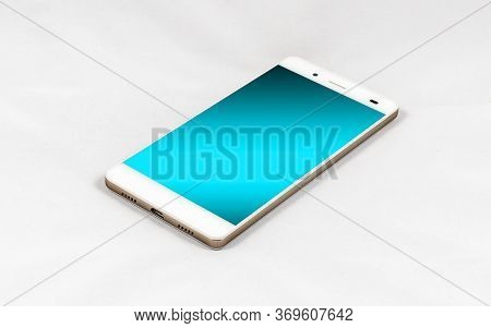 Modern Smartphone With Blank Blue Screen, Lies On The Surface, Isolated On White Background