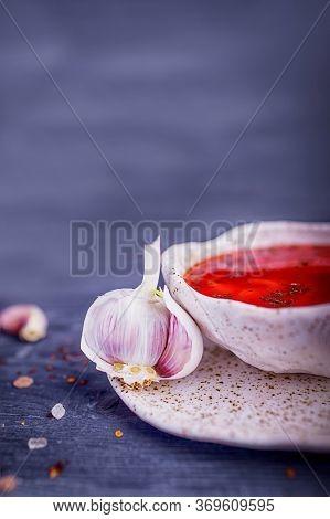 Garlic And Ukrainian Borsch Or Red Soup On A Gray Wooden Background. Ukrainian Cuisine, Copy Space