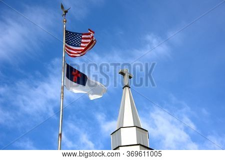 American And Christian Flag Fly Besides A Church Steeple With A Cross Symbol On Top.  Blue Skies And