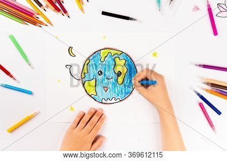 Child Girl Draws Planet Earth With Multicolored Felt-tip Pens On A White Sheet.