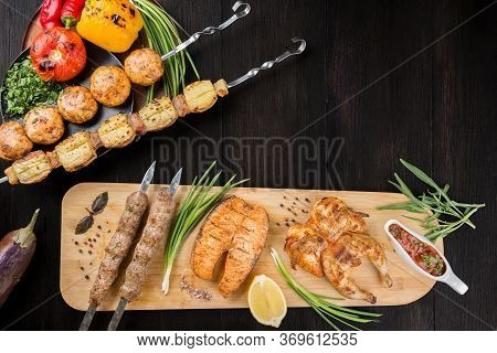 Assorted Grilled Meat Delicacies And Vegetables. Salmon Steak, Kebab And Chicken On A Wooden Board.