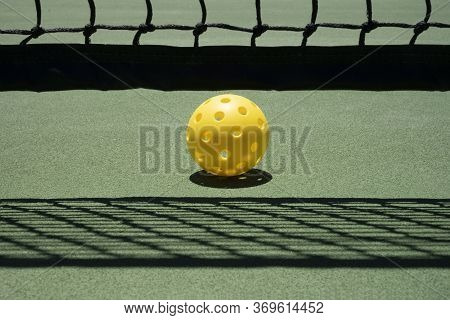 Pickleball On Court Near Net With Shadows