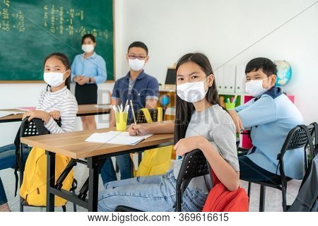 Group Of Asian Elementary School Students And Teacher Wearing Hygienic Mask To Prevent The Outbreak