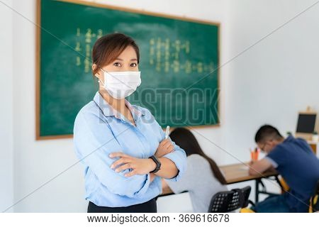 Asian Woman Teacher Wearing Masks To Prevent The Outbreak Of Covid 19 In Classroom With Student Whil
