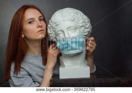 Red-haired Young Girl A Black Background A Gray T-shirt And Plaster Bust In Protective Medical Mask