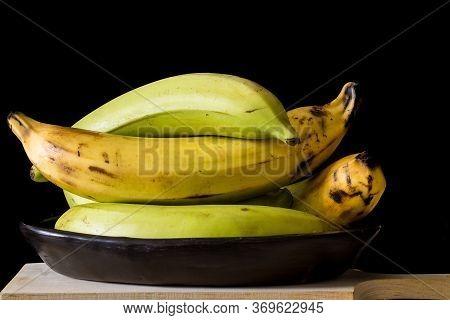 Plantain Or Green Banana (musa X Paradisiaca) In A Ceramic Traditional Dish On Dark Background