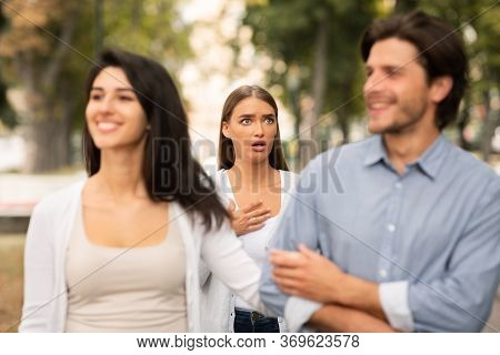 Infidelity Concept. Shocked Woman Seeing Cheating Boyfriend Dating With Other Girl Having Affair Wal