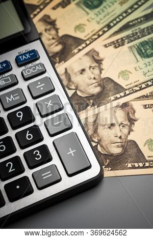 calculator with  us dollars on desk.