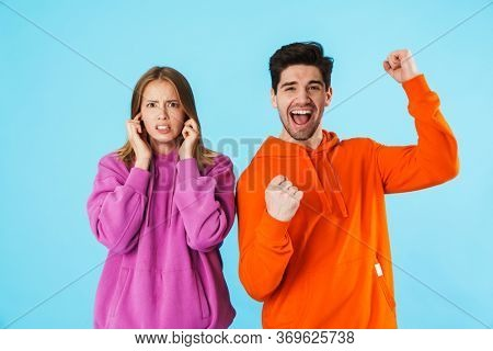 Portrait of a young couple wearing hoodies standing isolated over blue background, happy man celebrating success, upset woman covering ears
