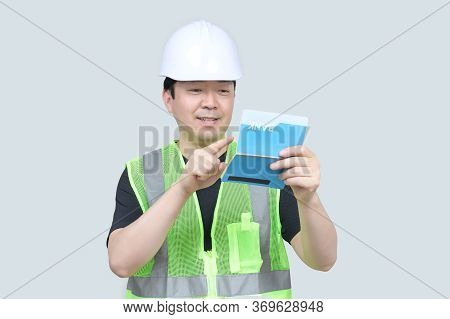 A Middle-aged Asian Engineer Holding A Bank Passbook In His Hand On A Gray Background.