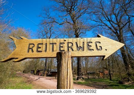 Signpost For A Riding Trail In A Forest Near Magdeburg In Germany. Sign With The Inscription Riding