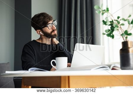 Image of young serious man using wireless earphones and working with laptop while sitting at table in living room