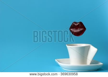Appetizing Caramel Lips Are Isolated On A Blue Background Over A Coffee Cup. The Concept Of Lip Augm