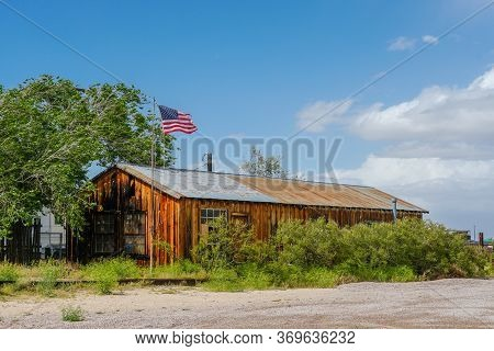 Old Wood Ranch With American Flag In The Desert Next National Trails Hwy, Amboy, California, Usa. Ma