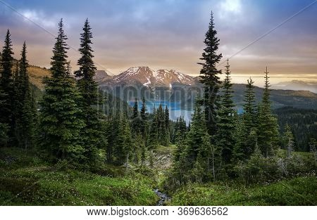Glacial Mountain Garibaldi Lake With Turquoise Water In The Middle Of Coniferous Forest At Sunset. V