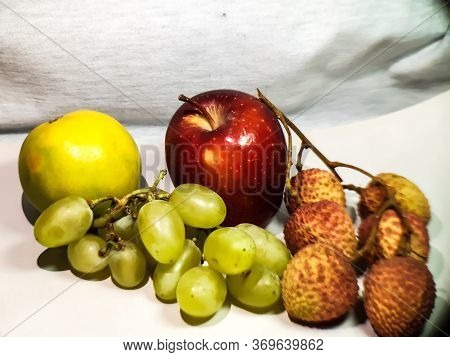 There Are Red Apples, Ripe Lemons, Ripe Litchis And Ripe Grapes On A White Background. This Is A Pic