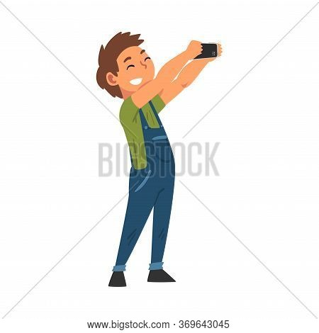 Smiling Boy In Overalls Taking Selfie Photo, Cute Child Character Photographing Himself With Smartph