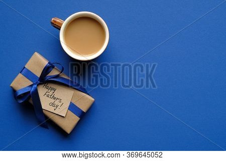 Happy Fathers Day Concept. Flat Lay Composition With Gift Box Wrapped Craft Paper With Blue Ribbon A