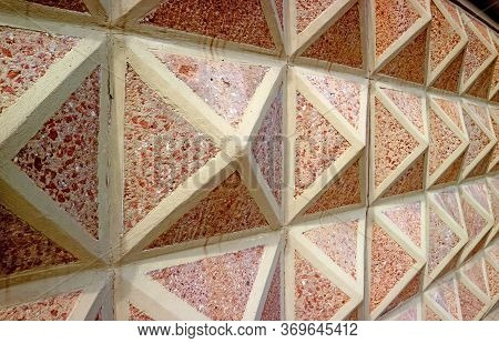 Diminishing Perspective Of Geometric Patterned Concrete With Red Stones Wall