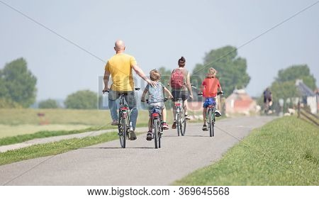Cyclists Cycling On A Dyke, Friesland, The Netherlands