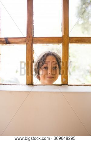 A Curious Boy Looks Out The Window, A Child Peeps Into The House Through The Window, Playful Kid, Po