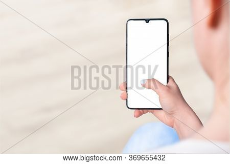 Woman Sitting And Holding Blank Screen Mock Up Mobile Phone, Woman's Hand Holding Cell Phone With Bl