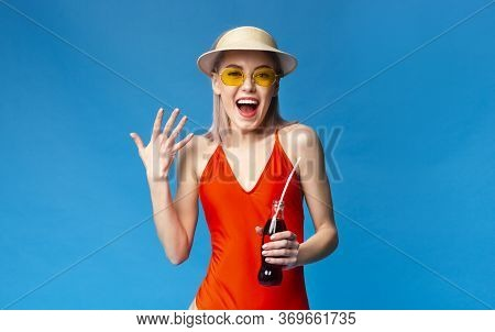 Refreshing Drink. Excited Millennial Girl In Swimsuit Enjoying Sparkly Summer Beverage, Holding Bott
