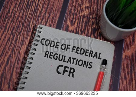 Book About Code Of Federal Regulations - Cfr Isolated On Wooden Table.