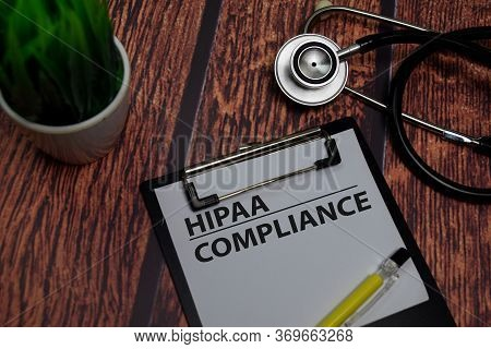 Hipaa Compliance Write On Paperwork Isolated On Wooden Table.