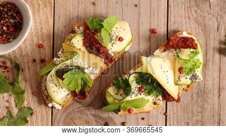 bread slice with zucchini, cheese, dry tomato and cheese cream
