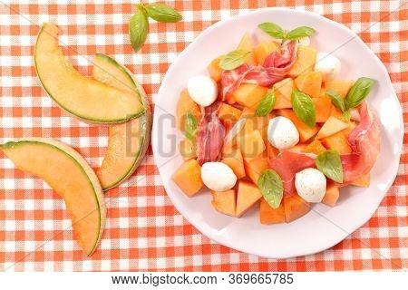 melon salad with prosciutto ham, basil and mozzarella
