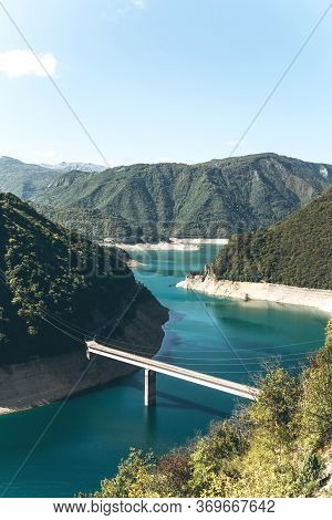 Beautiful View Of The Natural Landscape In Montenegro. Piva Reservoir With Turquoise Water And A Bri