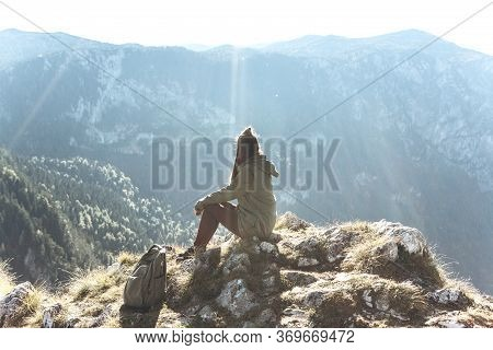 A Girl Tourist Or Traveler Sitting On A Peak In Solitude Enjoys Silence And Beautiful Views Of The M