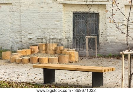Empty Wooden Bench Beside Leafless Young Tree Against Sandbox With Stump Fence Near Aged Building Wi