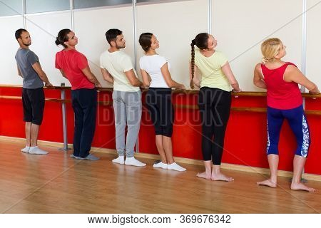 Group Of Smiling Russian Men And Women Practicing At The Ballet Barre