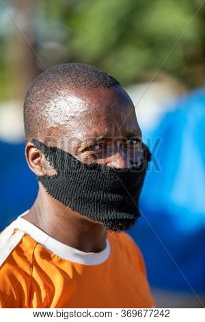 Young African man wearing a improvised face mask in the village