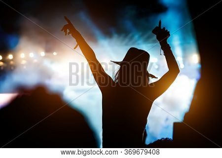 Silhouette Of Girl With Raised Hands On Music Concert