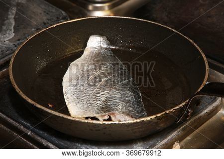 A Fresh Sea Bass Frying In A Pan With A Little Oil