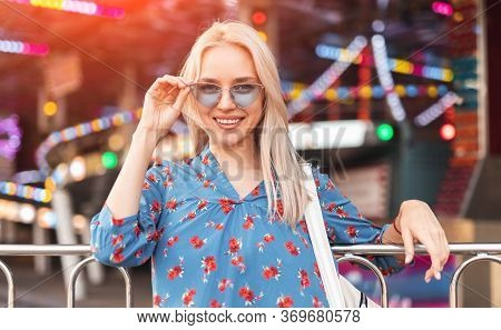 Relaxed Blond Female In Trendy Blue Sunglasses And Casual Dress Smiling On Fairground