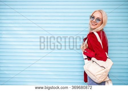 Side View Of Cool Millennial Woman In Trendy Sunglasses And Red Jacket With Handbag Looking Over Sho