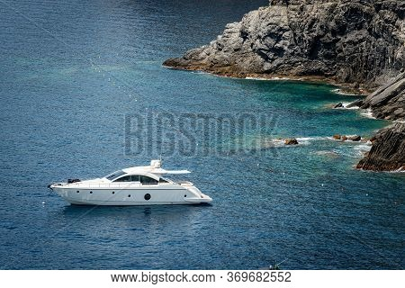 White Motor Yacht Anchored In The Port Of Vernazza. Coastline Of The Cinque Terre And Mediterranean